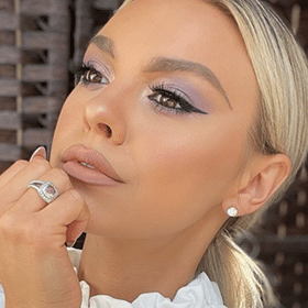 Close up of womans face with her hand on her chin looking off to the distance, blue and purple eye shadow with long lashes and liner