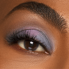 Close up of womans eye with blue and purple eye shadow with full lashes