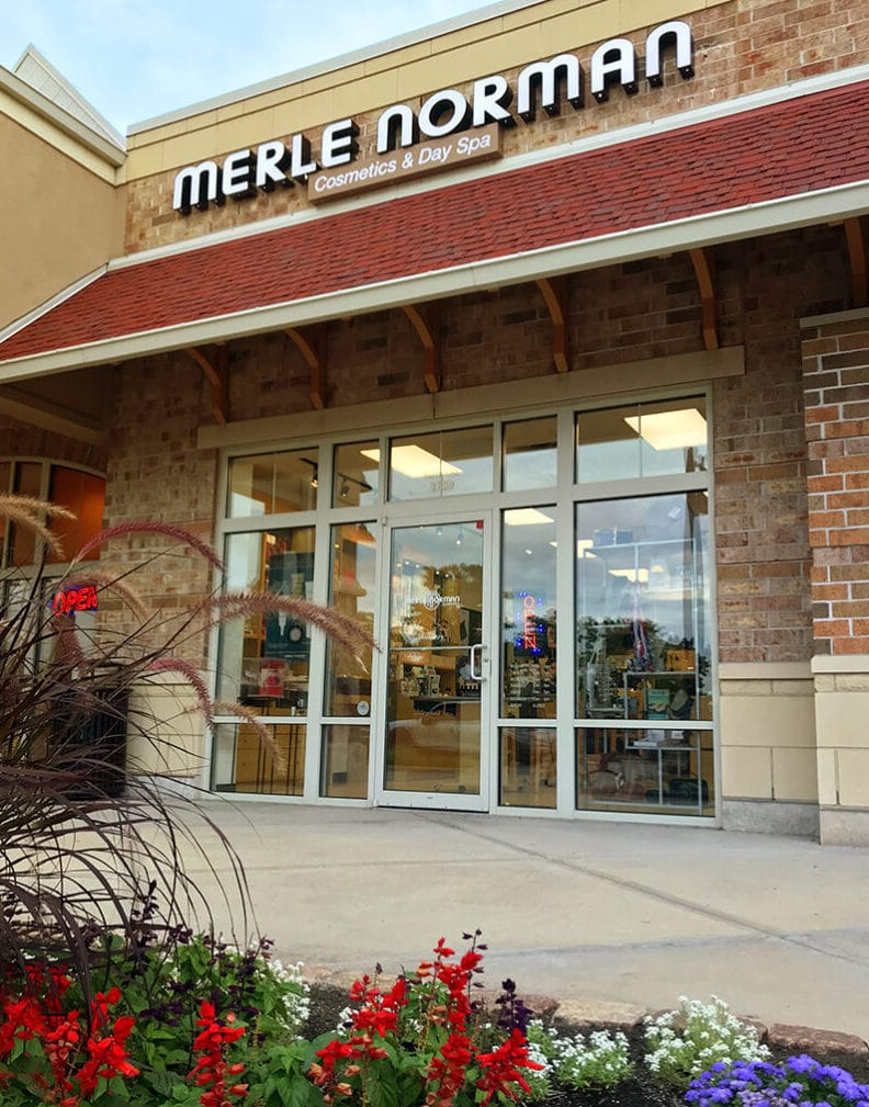Front of Merle Norman store, brick store with sign above and garden in front